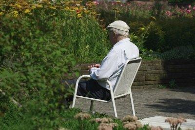 Ein Senior draußen in einem Gartenstuhl