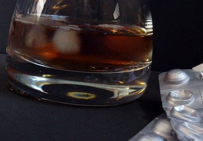Ein Glass mit Alkohol drin mit Medikamenten daneben