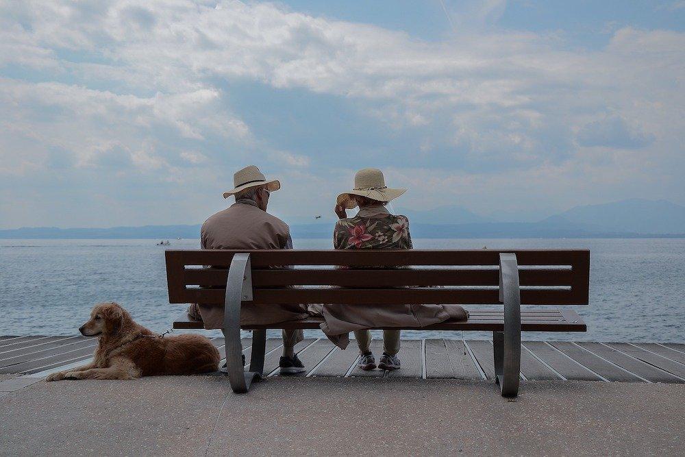 Ein älteres paar auf einer Sitzbank mit einem Hund