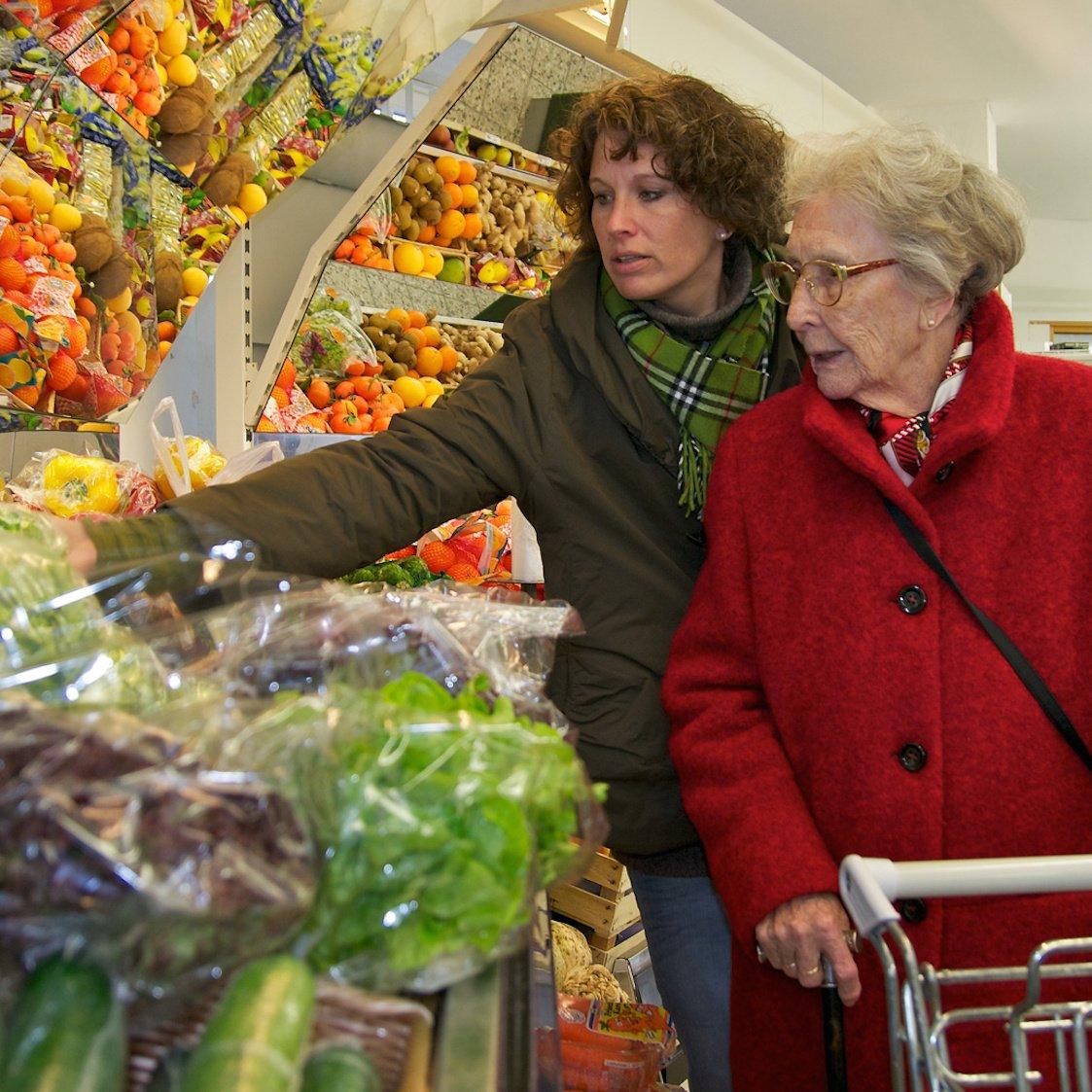 Ältere Dame beim Einkaufen mit einer Betreuerin