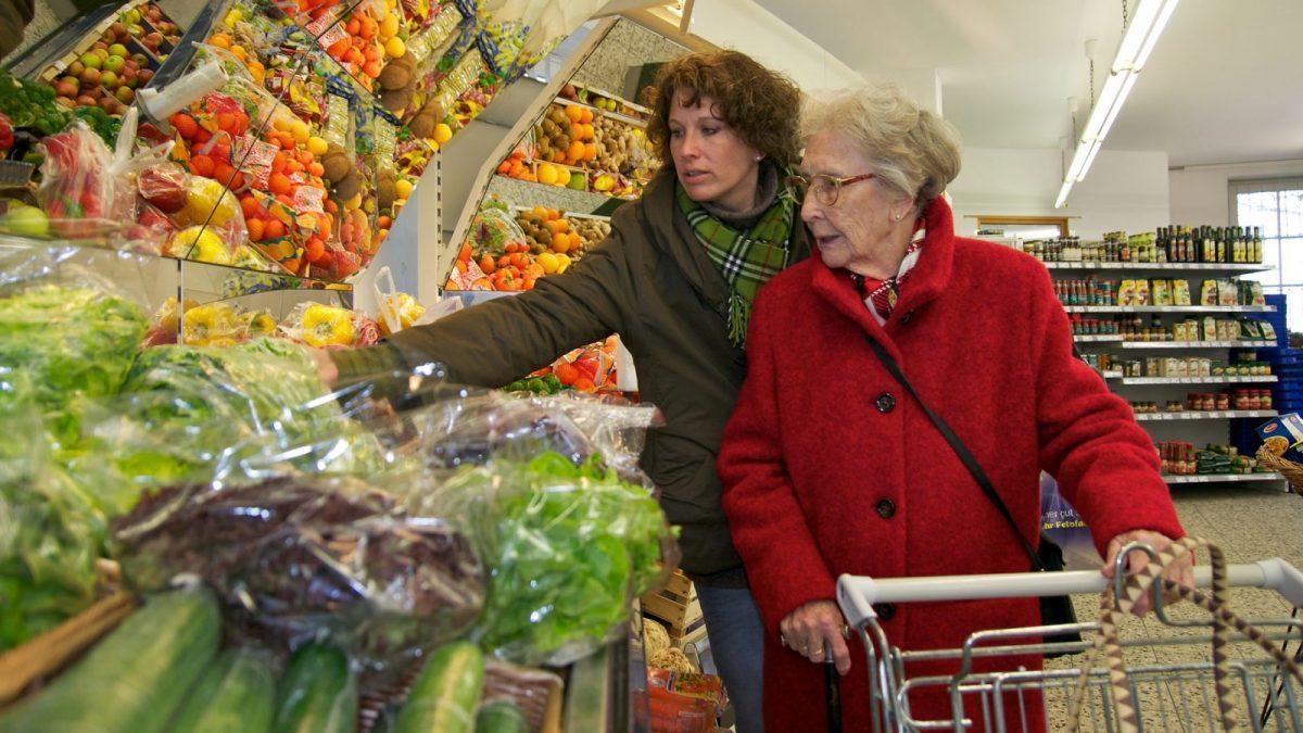 Seniorin wird beim Einkaufen von einer jüngeren Frau begleitet