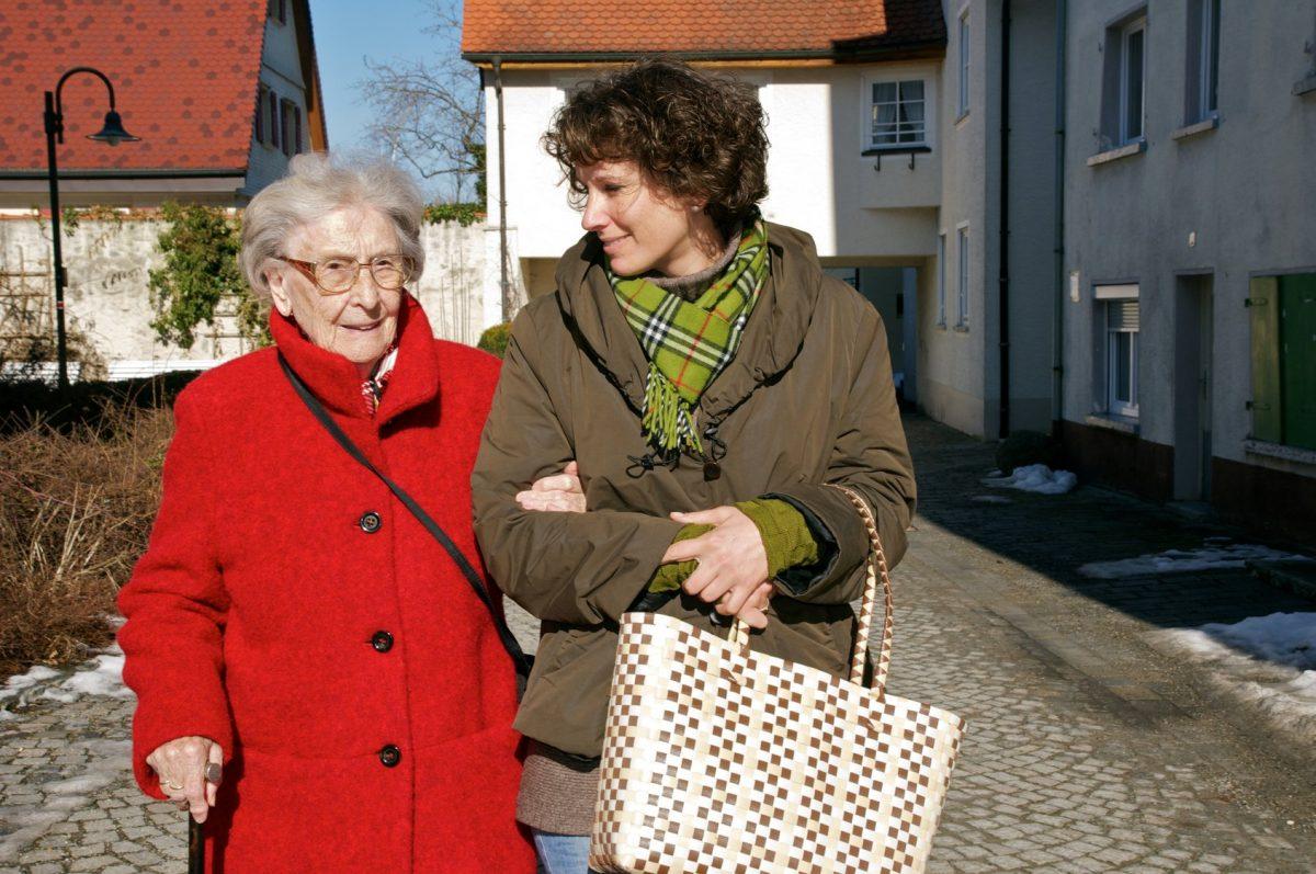 Eine Seniorin wird von einer jüngeren Frau beim Spazieren begleitet