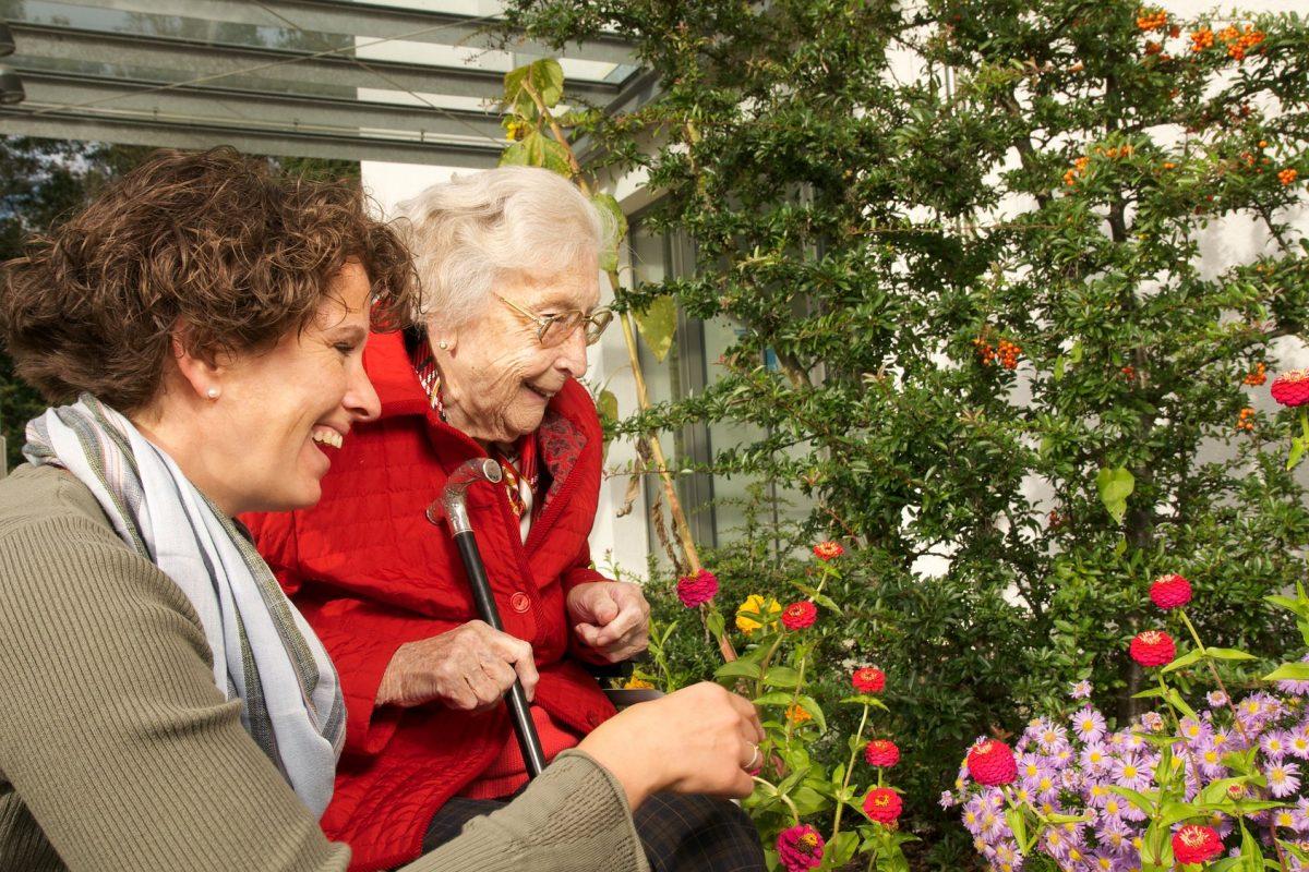 Eine Seniorin und eine jüngere Frau schauen sich die Blumen im Garten an