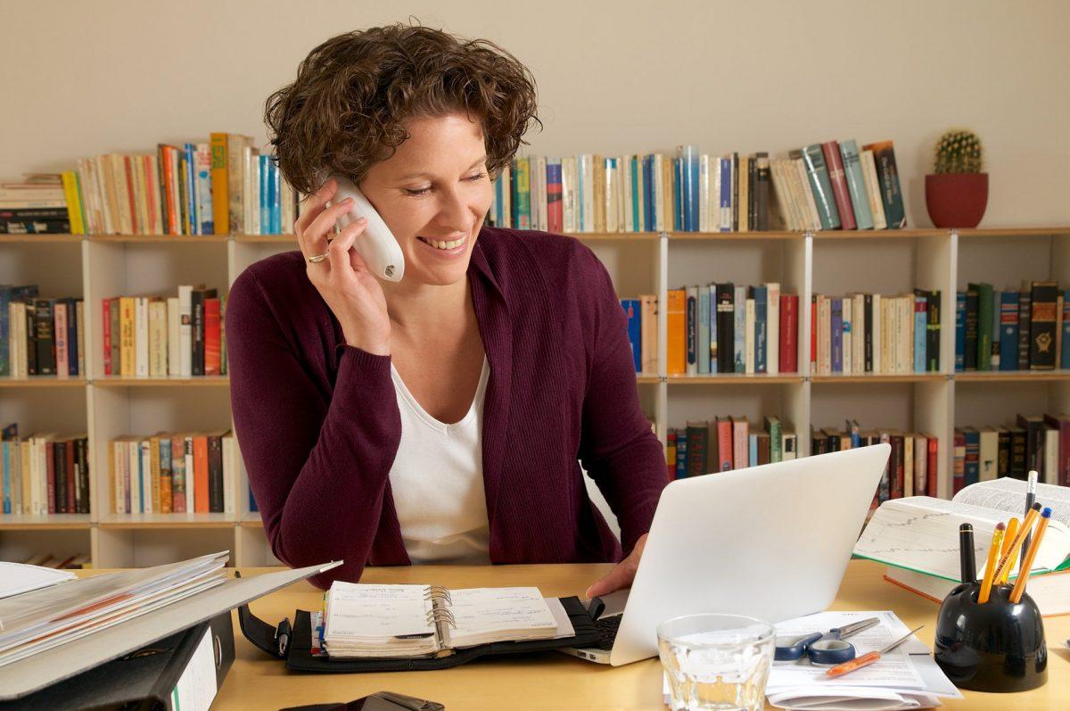 Junge Frau telefoniert am Schreibtisch mit einem Laptop drauf