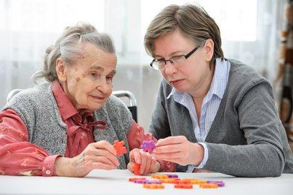 Eine Frau puzzelt zusammen mit einer Seniorin