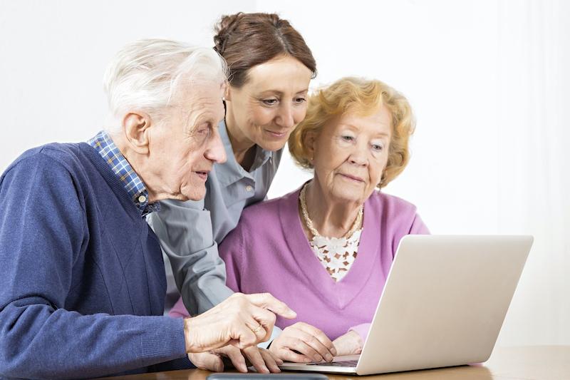 Eine Seniorin im Sessel wird von einer Frau von hinten umarmt