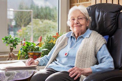 Eine Seniorin sicher im Sessel mit Ihrem Hausnotruf Knopf.