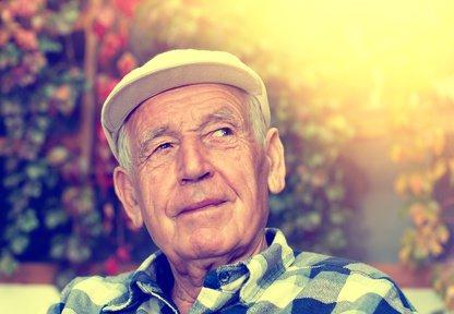 Ein nachdenklicher Senior in einem karierten Hemd und einer Mütze auf
