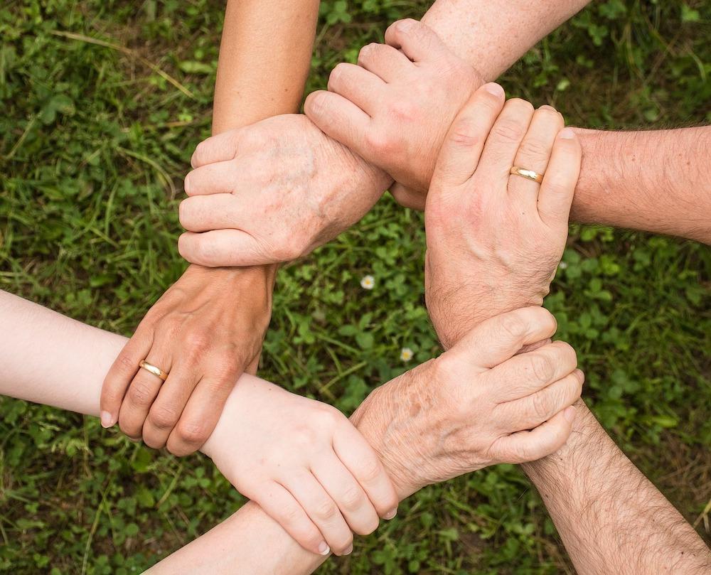 Ein Kreis aus Händen die sich am Handgelenk halten