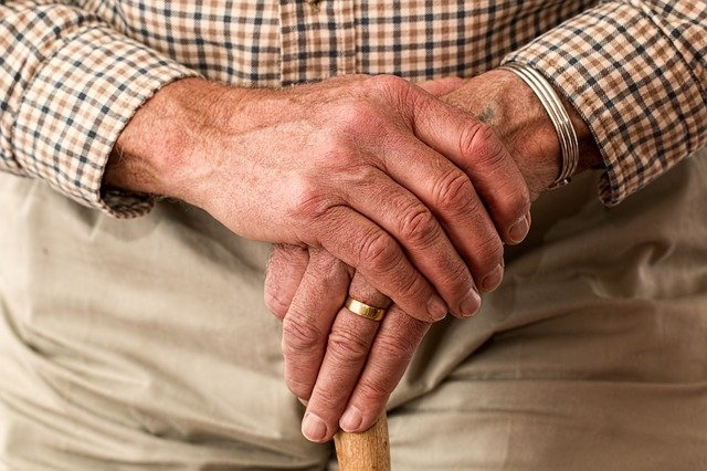 Seniorenhände an einem Gehstock