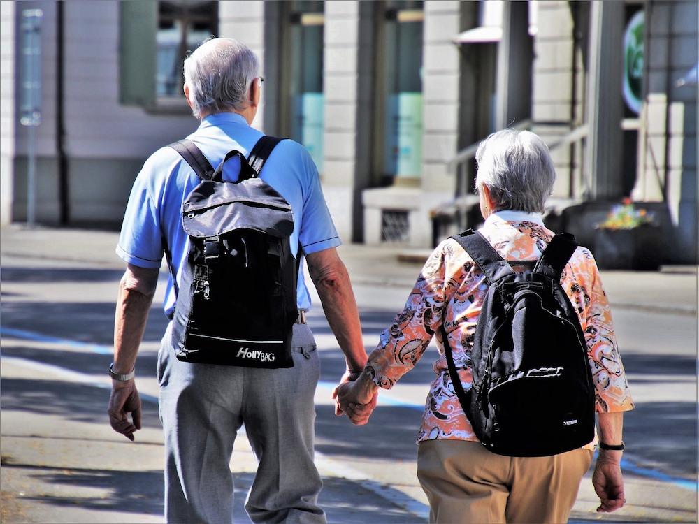 Ein Seniorenpaar mit Rücksäcken auf bei einem Spaziergang