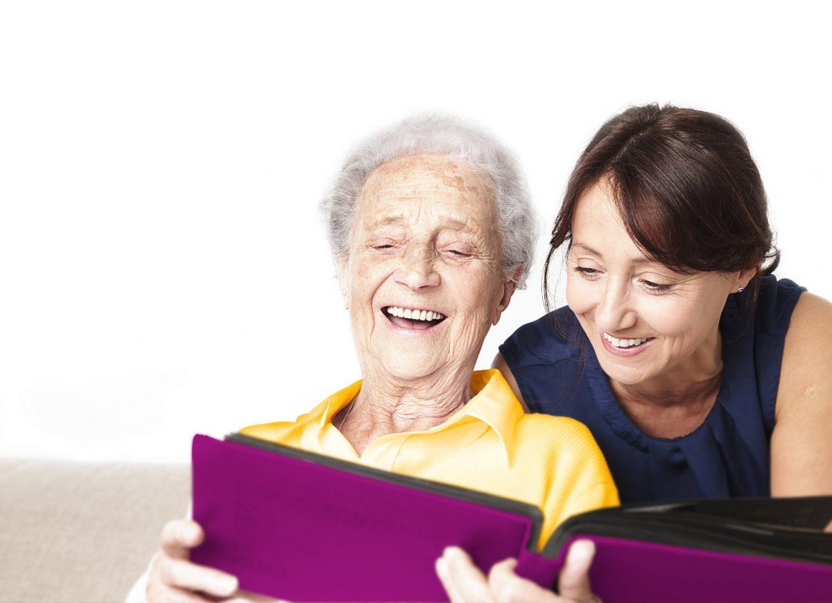 Eine Seniorin sitz in einem Sessel und schaut sich ein Album mit einer jüngeren Frau an