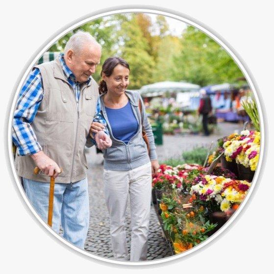 Eine Frau begleitet einen Senior beim Einkaufen