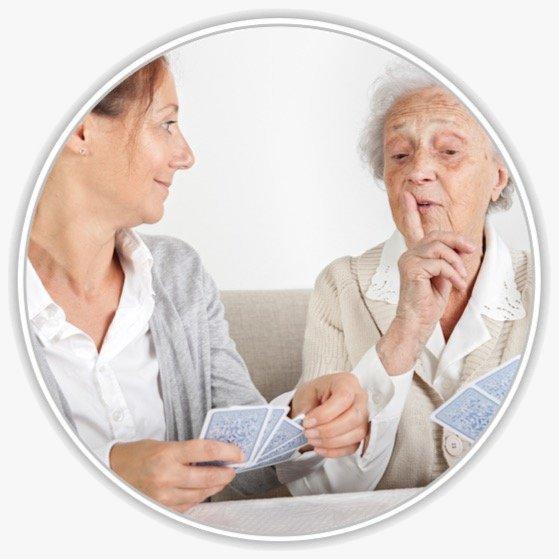 Eine junge Frau spielt Karten mit einer Seniorin