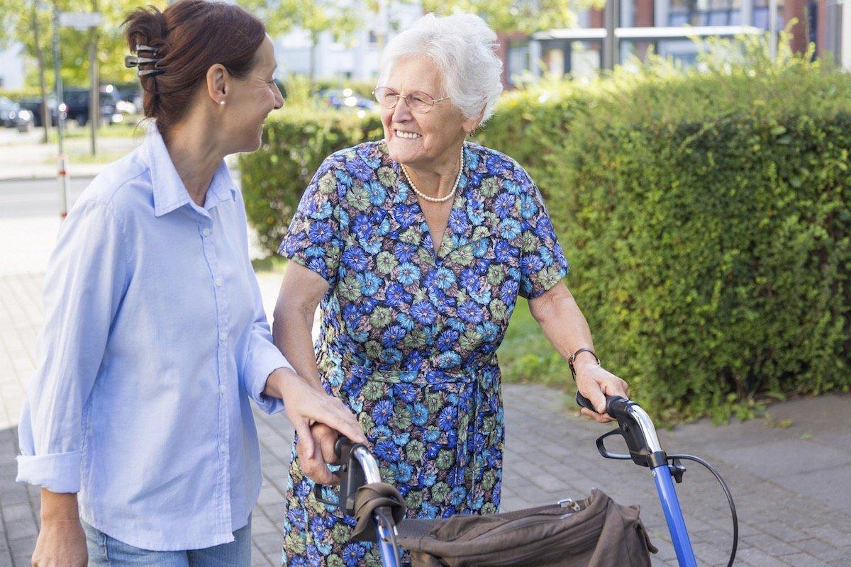 Eine Seniorin mit einem Rollator begleitet von einer jüngeren Frau bei einem Spaziergang